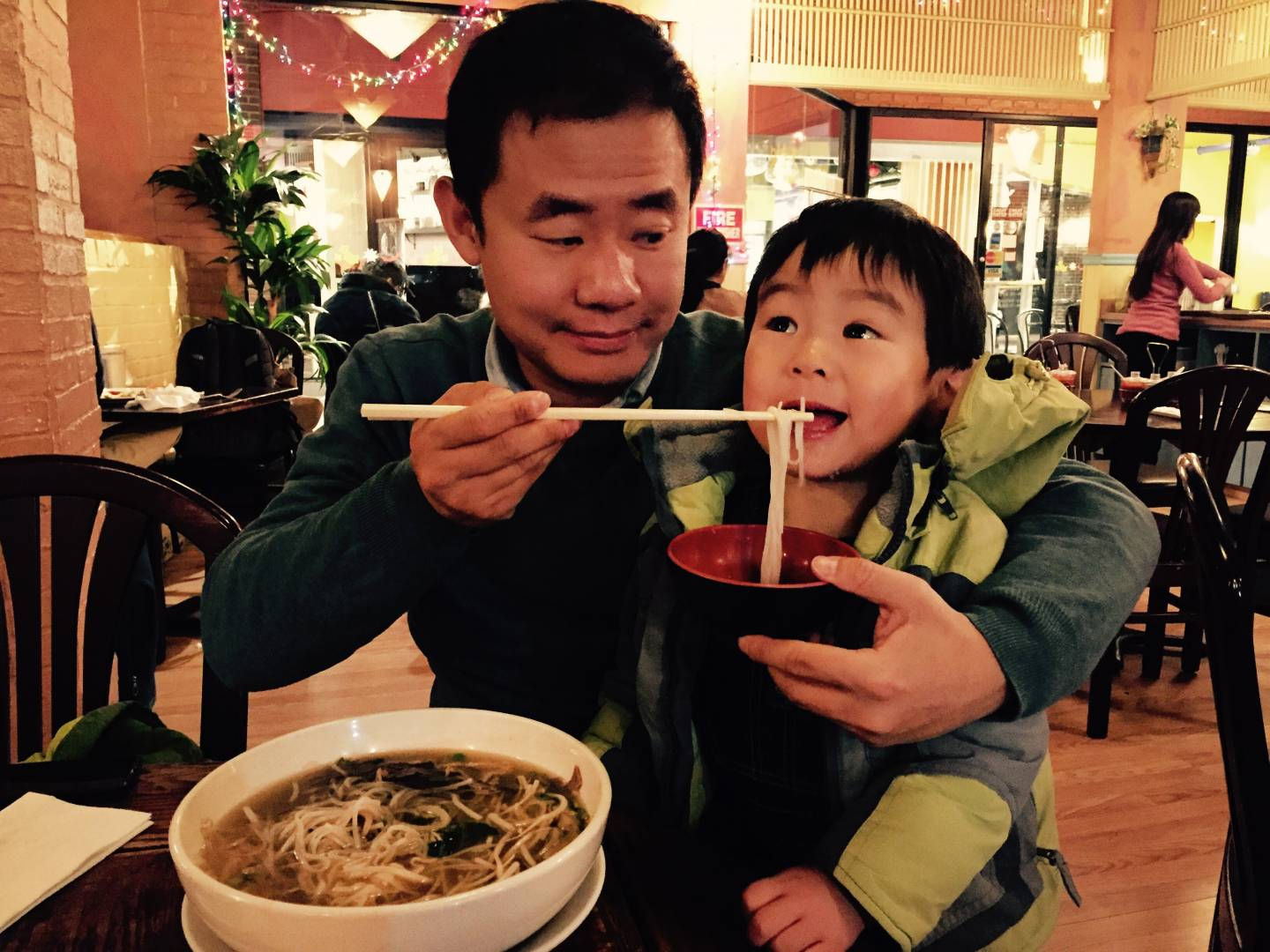 Wang enjoys a meal of noodles with his young son.
