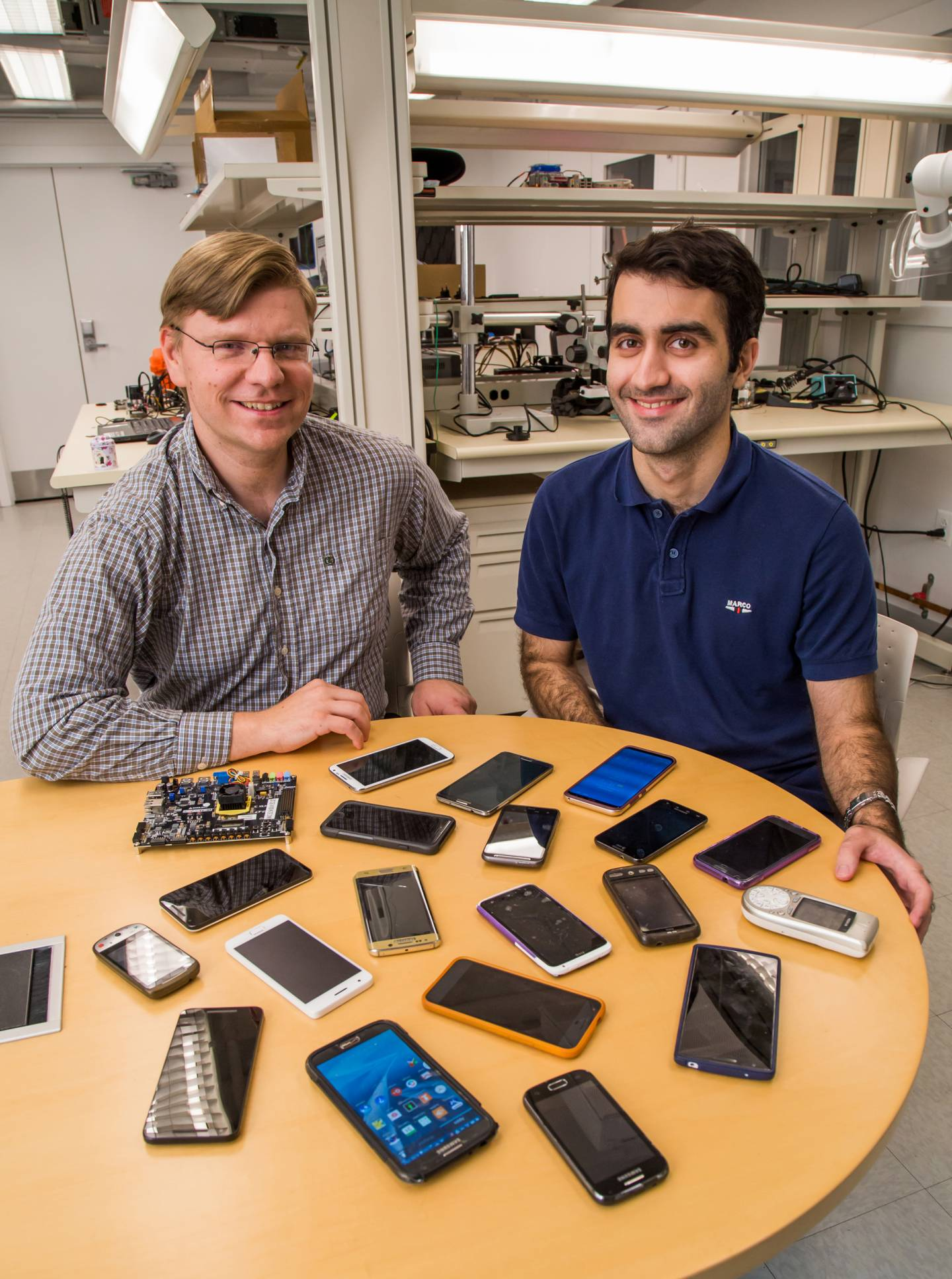David Wentzlaff and Mohammad Shahrad sit with smart phones on a table