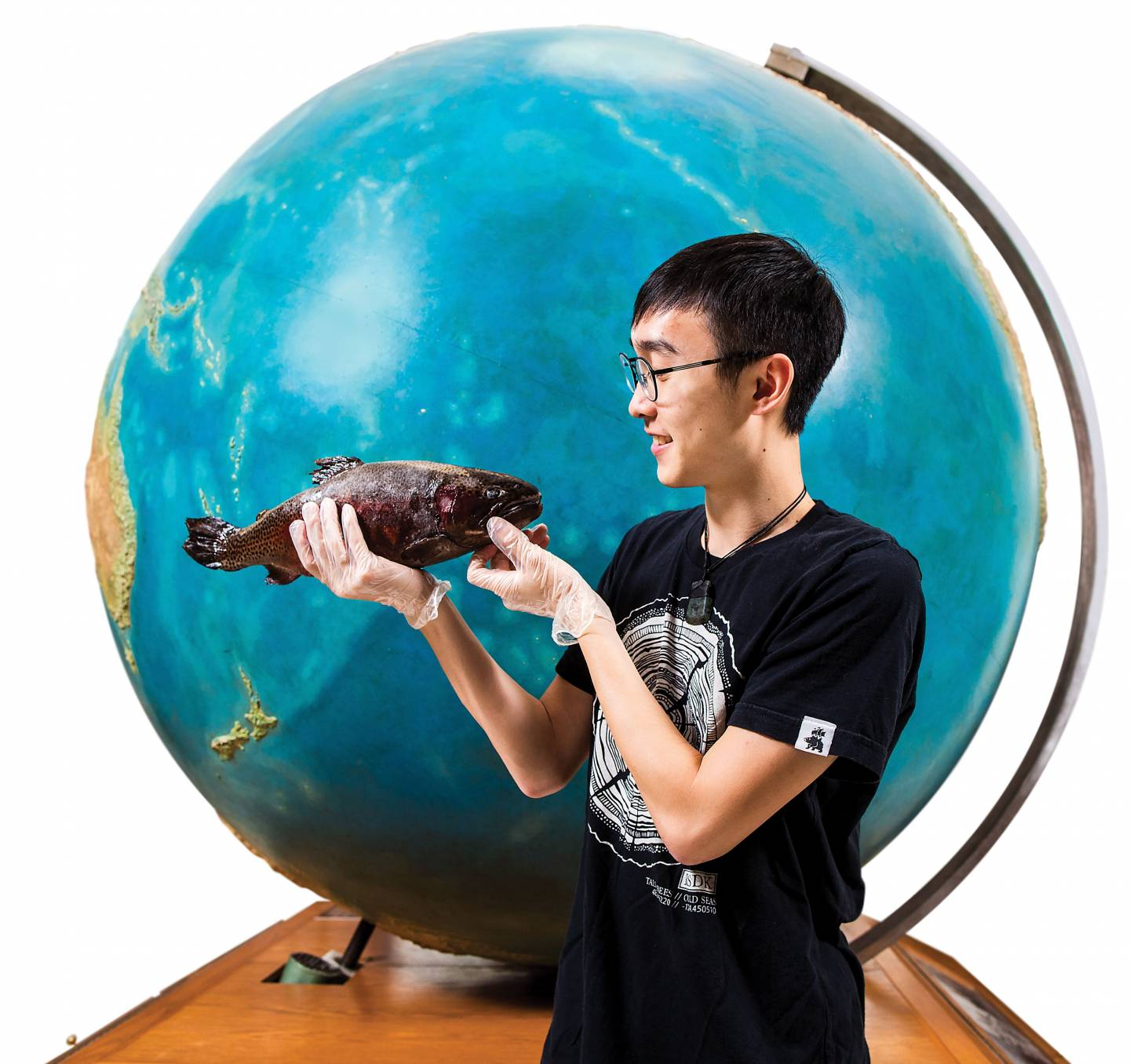 Keo Chan holding fish standing in front of globe