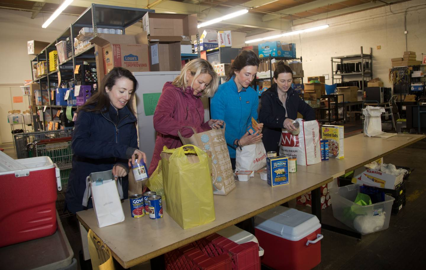 Kaitlin Lutz, Debby Foster, Jaclyn Sweet and Leslie Rowley pack bags of food
