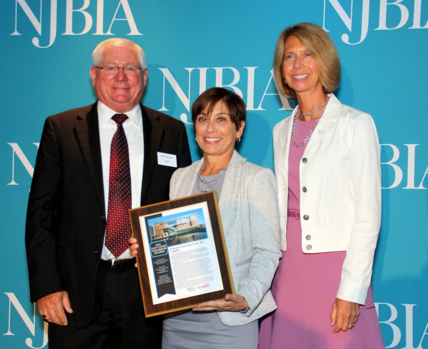 Karen Jezierny holds the NJBIA Good Neighbor Award with Matthew Wright and Michele Siekerka