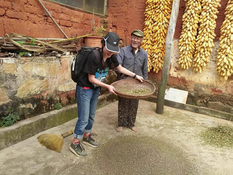 Kisara Moore sifting buckwheat in Kunming, China next to an elderly Chinese man