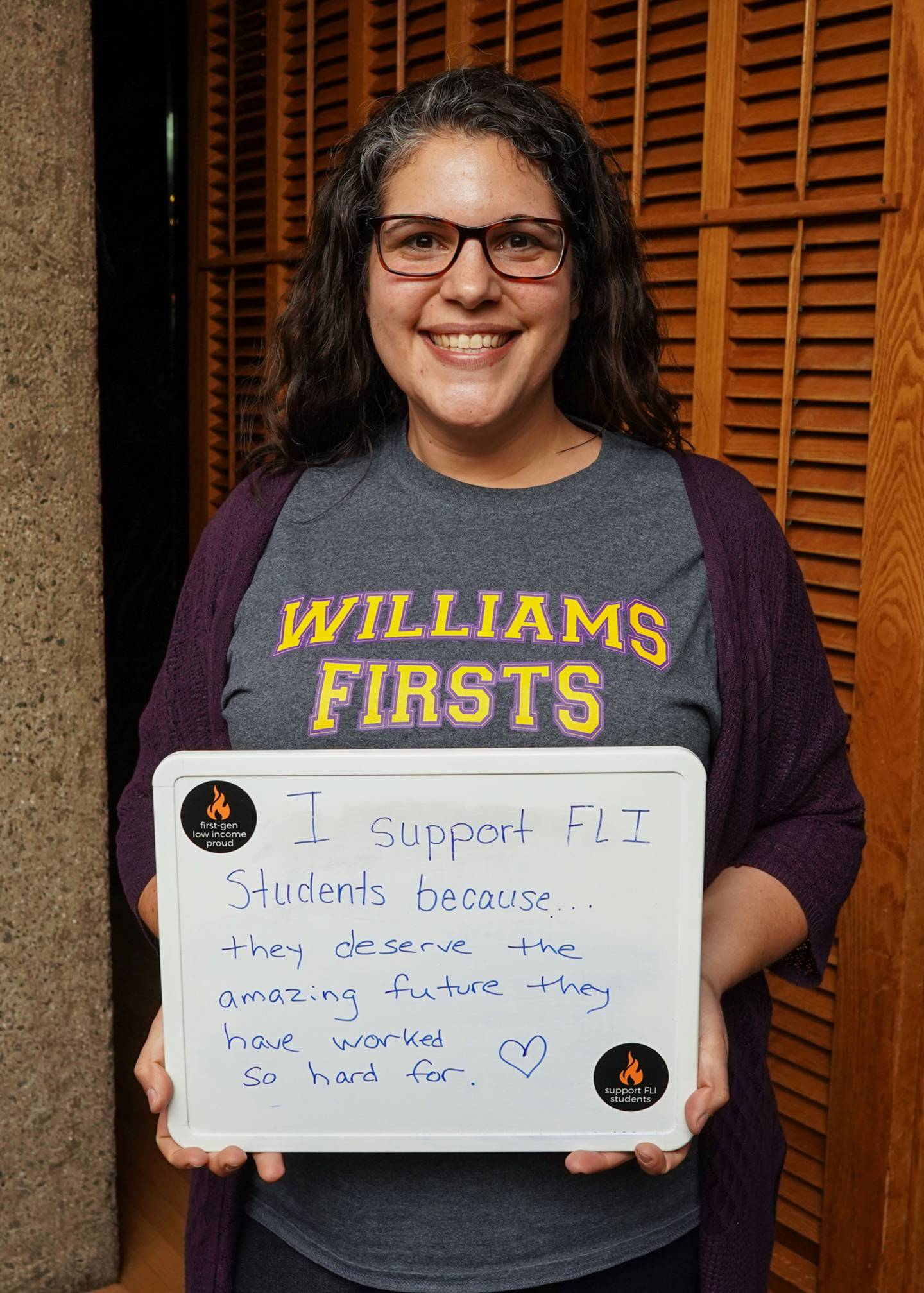 "April Ruiz holding a whiteboard that says ""I support FLI students because they deserve the amazing future they have worked so hard for."""