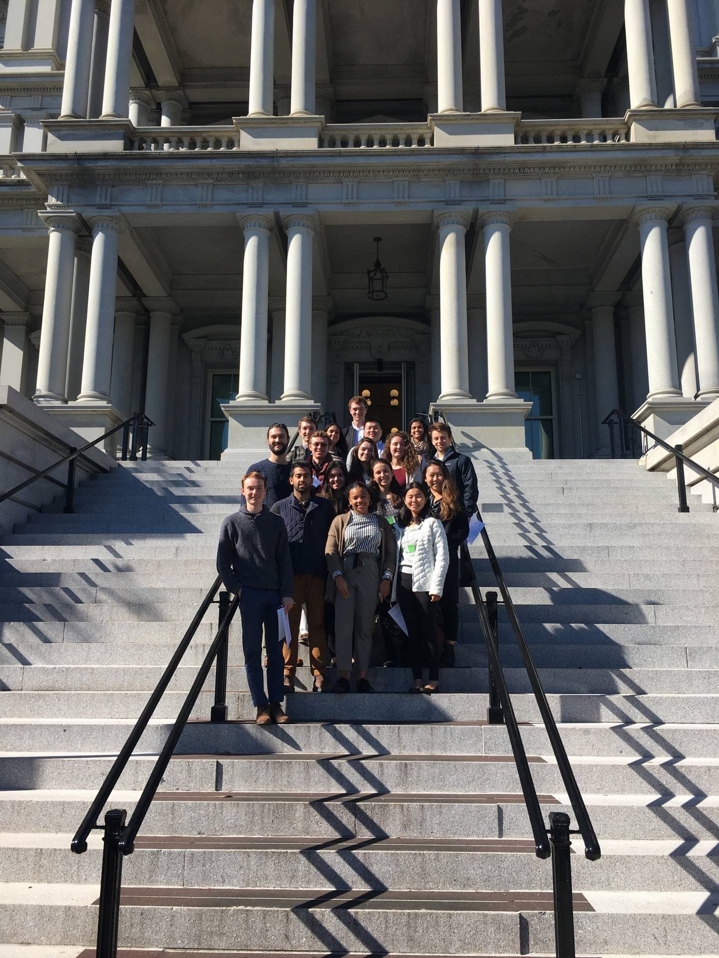 A group of students pose for a photo on the steps of the Eisenhower Executive Office Building in Washington DC