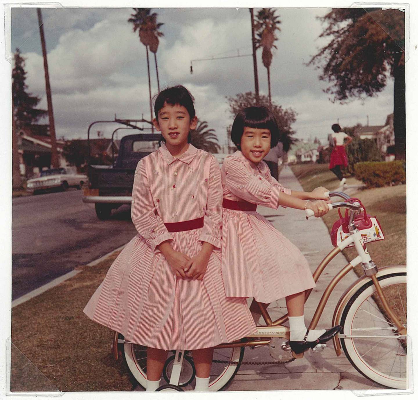 Two girls in pink dresses with bicycles on Los Angeles sidewalk