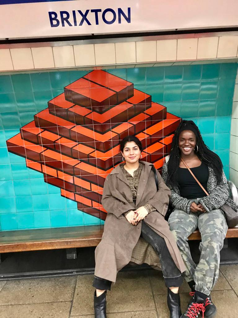 Two women sitting on a bench at a subway station