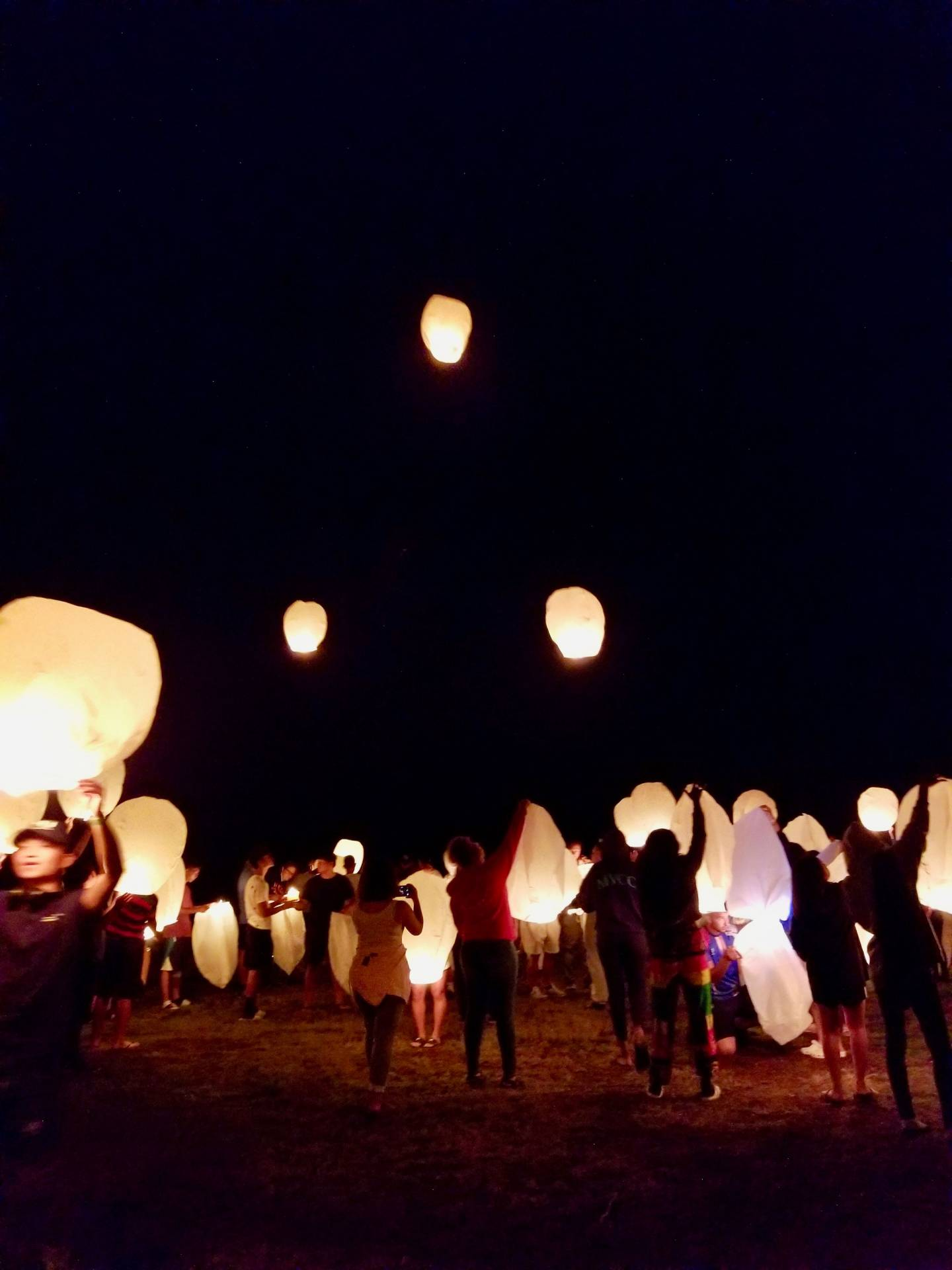 Campers releasing paper lanterns into the sky