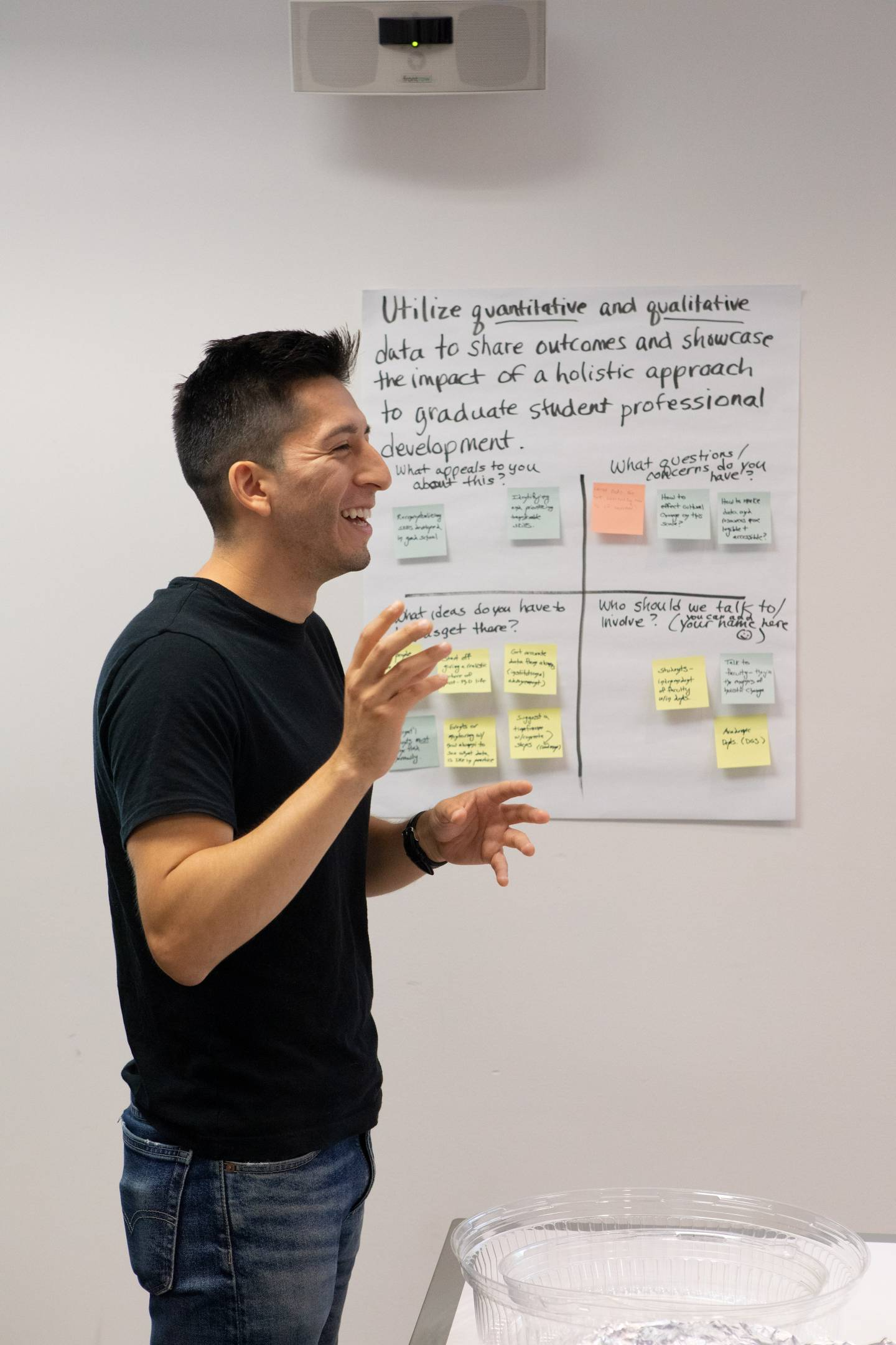 A student gesticulates and speaks with a handwritten chart in the background