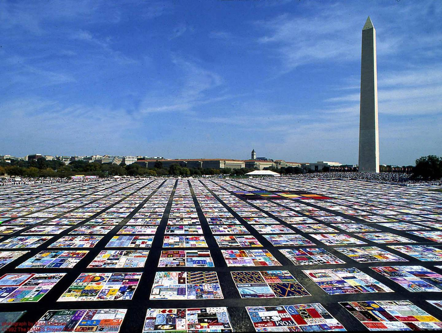 Display of AIDS quilts stretching out towards the horizon with Washington Monument in the background