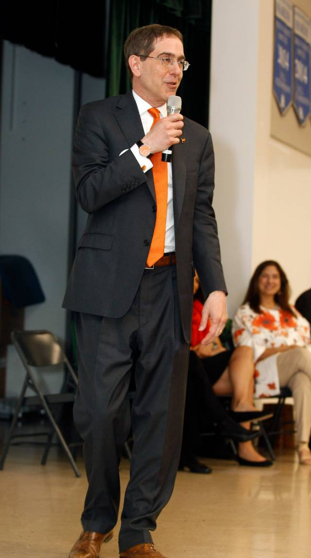 Christopher L. Eisgruber stands on stage with a microphone, speaking