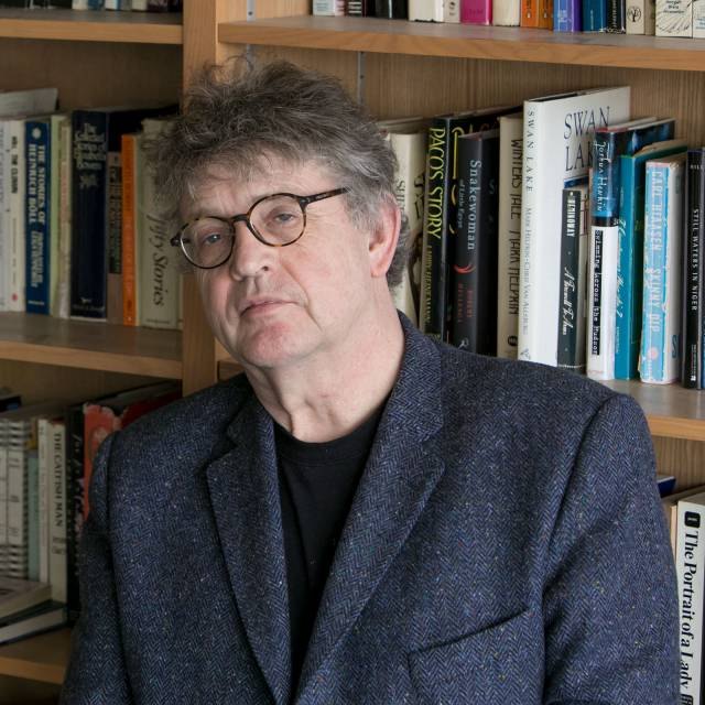 Paul Muldoon with bookshelves in background