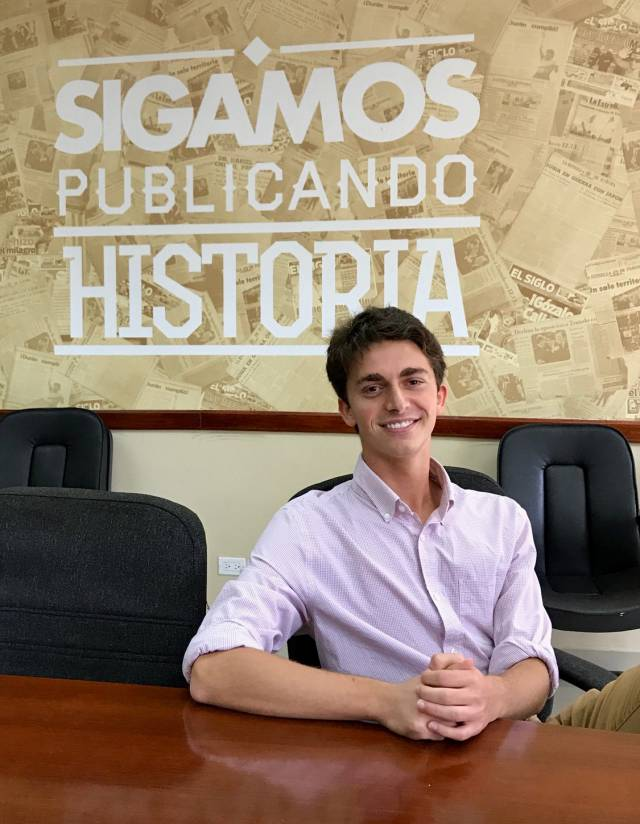 "Jordan Salama in front of a wall that says ""Sigamos Publicando Historia"""