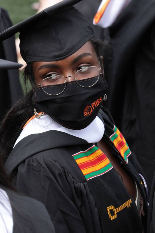 A graduating student wearing a Pan-African scarf and a PIIRS mask